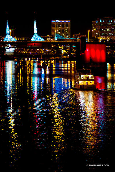 BOAT APPROACHING A CITY BRIDGE WILLAMETTE RIVER DOWNTOWN PORTLAND OREGON AT NIGHT VERTICAL COLOR