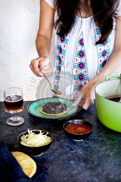 A women is spooning salsa over homemade Black Beans that are served with corn tortillas, salsa, cheese and beer.
