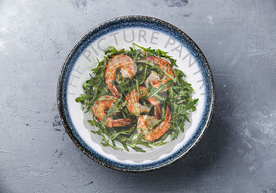 Arugula salad with prawn shrimp on gray concrete background
