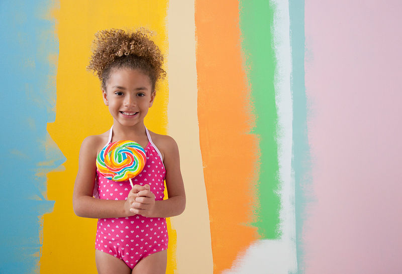 Young girl against multiple color painted wall.