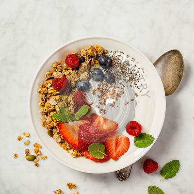 Bowl of homemade granola with yogurt and fresh berries