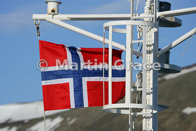 The flag of Svalbard (and Norway) being flown on the mast of a ship at anchor in Longyearbyen harbour, Svalbard