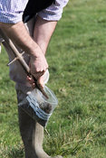 Agricultural expert taking soil samples for testing off a pasture in the Yorkshire Dales, UK.