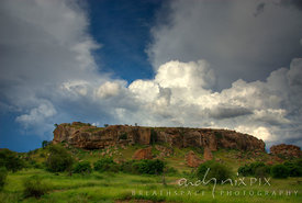 A single rock outcrop of historic Mapungubwe Hill, site of the capital of the earliest known kingdom in sub-Saharan Africa that flourished from 900AD to 1300AD, with lush green grass and bushes around the base and cumulonimbus thunder clouds above.