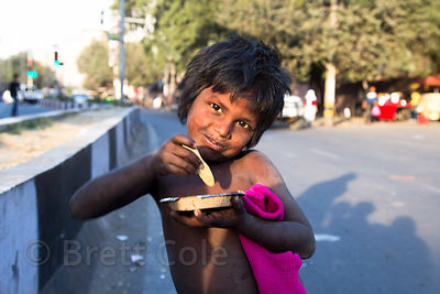 A dalit boy from Rajasthan eats a meal I gave him while begging near the New Delhi railway station, Delhi, India