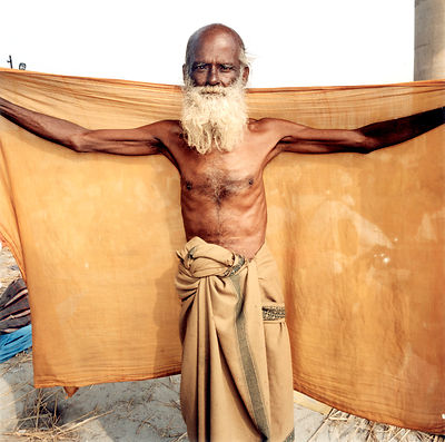 An elderly pilgrim dries himself with a yellow towel at the Kumbh Mela