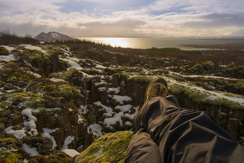 Mountain climber sits atop a mountain ledge with feet dangling off edge in Iceland. Adventure travel photography by Jason Tinacci