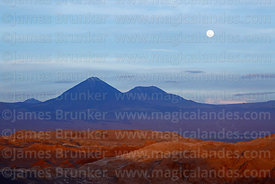 Full moon above Licancabur (L) and Juriques (R) volcanos, seen from Achaches viewpoint in Valle de la Luna, Los Flamencos National Reserve, Chile