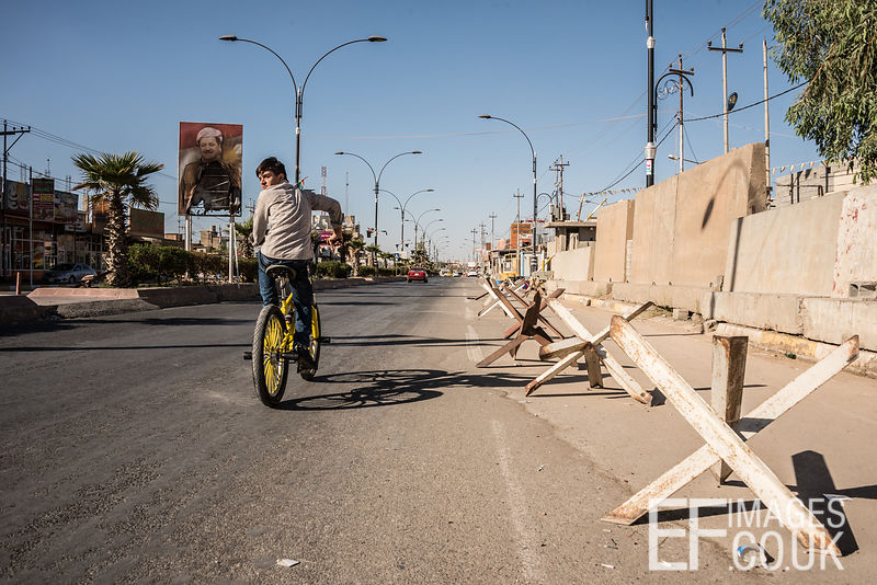 A boy cycles through the near deserted Kurdish quarter of Kirkuk, past a poster of Barzani that has been burned during the conflict over the past 48 hours. Kirkuk, Iraq, 17th October 2017