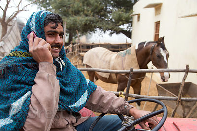 A farmer talks on his mobile phone while sitting proudly on his tractor in front of his favorite personal horse, Killa village Rajasthan, India