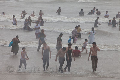 Families swim in the Arabian Sea at Juhu Beach, Mumbai, India, during a monsoon rain.
