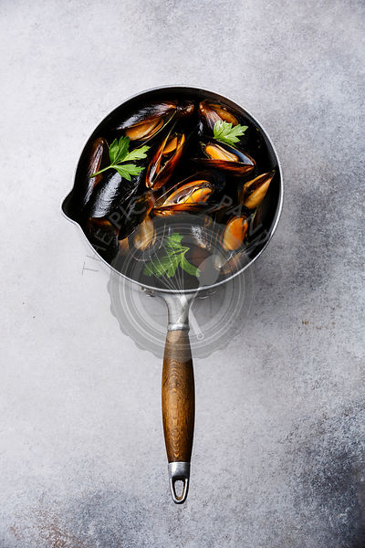 Mussels Clams in cooking pan with parsley on white background
