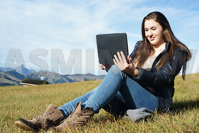 Girl with digital tablet in the mountains