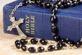 Rosary beads and cross lying on a bible.