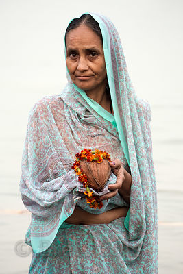A woman prays on the Ganges River during Chhath Puja, Varanasi, India. Chhath Puja is a devotion to the Sun God Surya in which people gather at sunset and then on the following sunrise and offer prayers.