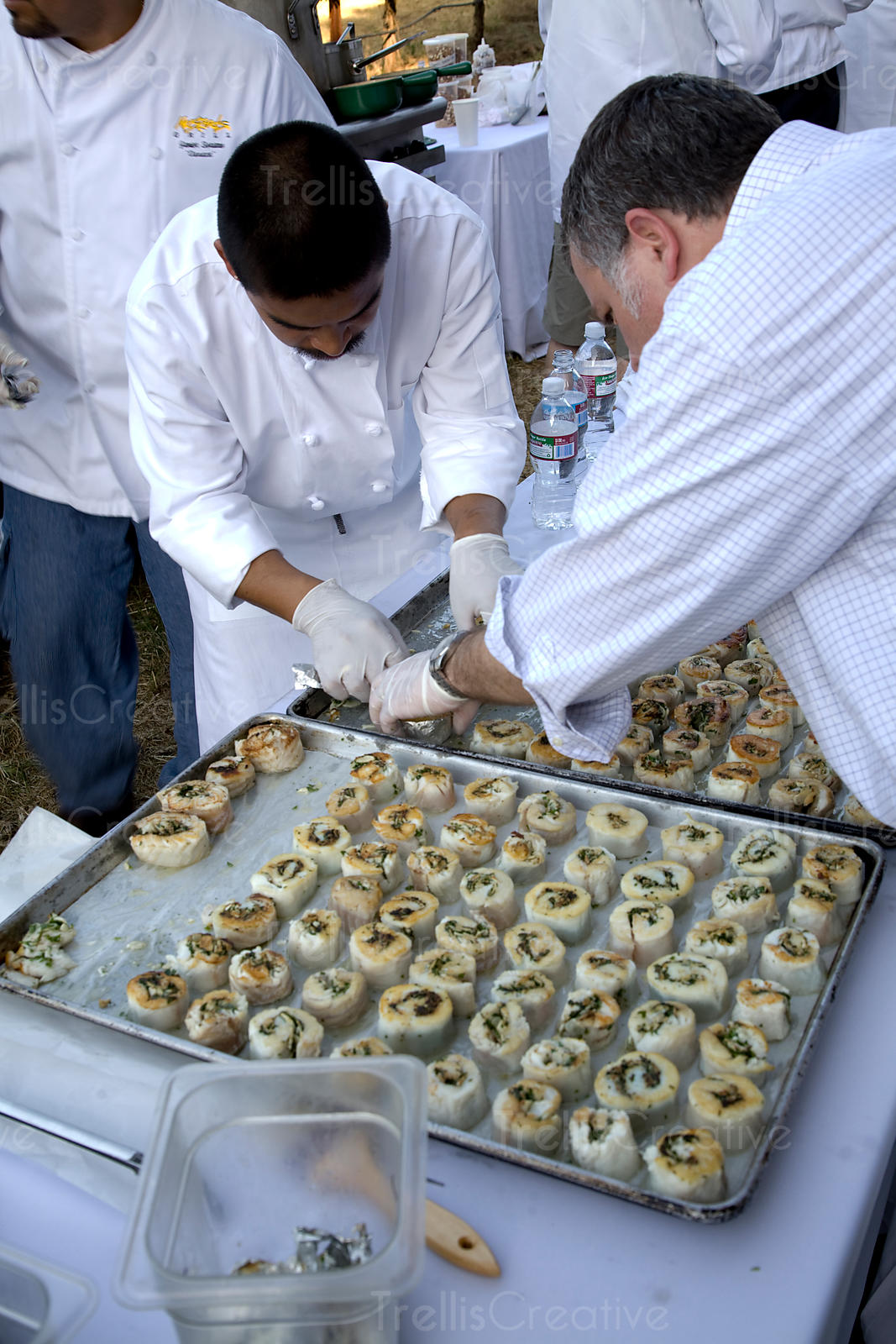 Two chefs prepare a tray of hors d'oeuvres