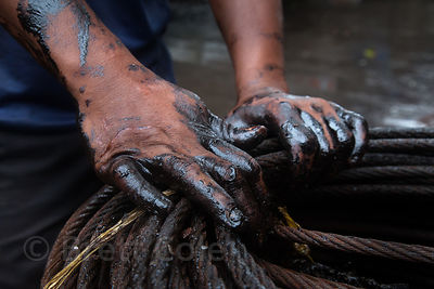A worker's greasy hands on steel cables at the Sassoon Docks fishing area, Mumbai, India.
