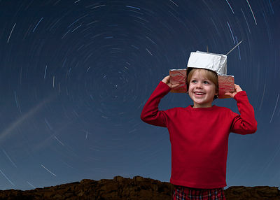 Boy with space hat and star trail in the sky