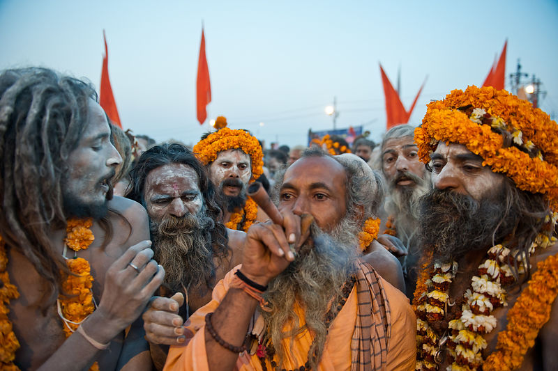 A saint smokes a pipe while others wait for their turn. This photograph was shot during a procession at the Kumbh Mela in Allahabad.
