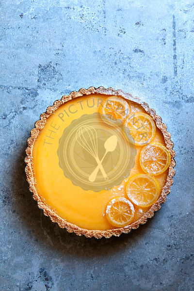 Classic lemon tart garnished with candied lemon slices.Top view