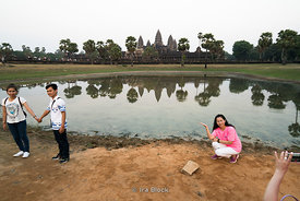 Tourists pose next to Angkor Wat in Siem Reap, Cambodia.