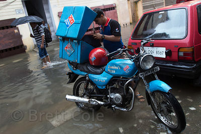 Domino's Pizza delivery motorcyle makes a delivery during monsoon flooding, Lake Gardens, Kolkata, India. Taken during the heaviest rains in Kolkata in a decade.