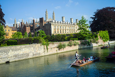 Punts and passengers glide past Clare College (founded 1326) on the  River Cam past the Garret Hostel bridge