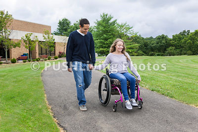 Young female student in a wheelchair on campus