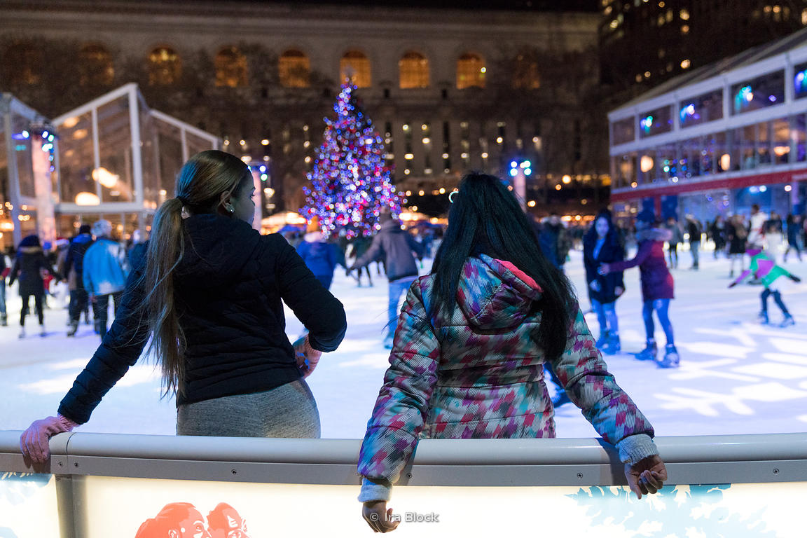 Two young girls pause for a break while skating on the ice rink at Bryant Park Winter Village in Manhattan, New York