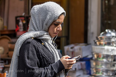 Young woman with covered head looking at cell phone in the spice market, Istanbul