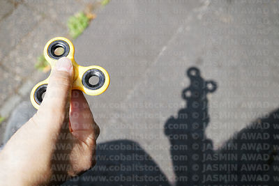 Yellow spinner outdoors with matching shadow