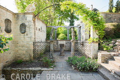 The Patio Garden, a small paved court, framed by wrought iron screens and a pair of Italian marble dancing figures. Iford Manor, Bradford-on-Avon, Wiltshire