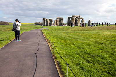 UK - Wiltshire - Tourists photograph themselves and the stones at the standing stone circle at Stonehenge