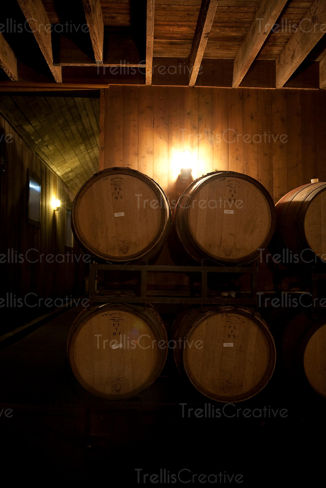 Stacked oak wood barrels in  winery cellar