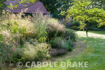 Central circular bed is a mass of graceful grasses and herbaceous perennials including Miscanthus 'Morning Light', Stipa gigantea and Calamagrostis x acutiflora 'Karl Foerster' with striking red tin roof on barn behind. At front Allium carinatum subsp pulchellum mingles with Eragrostis chloromelas and Sedum 'Ruby Glow'. Broughton Buildings, Broughton, nr Stockbridge, Hants, UK