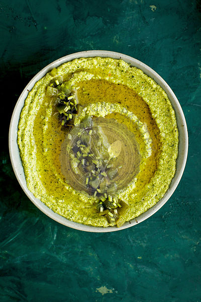 Roasted Poblano Cilantro Pesto in a ceramic bowl served with sourdough bread.  Photographed on a dark green background.