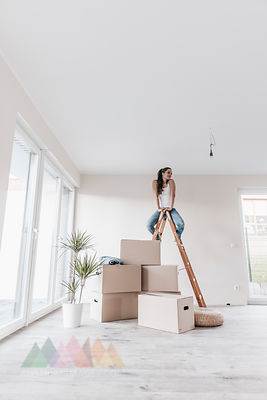Mature woman sitting on ladder in her new home