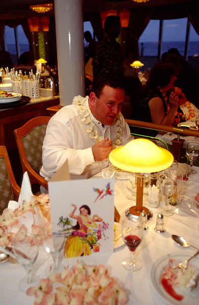 A guest eating his dinner at a Hawaiian party on board the P&O Cruise Liner Oriana