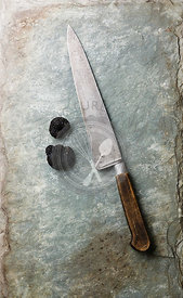 Black truffle and kitchen knife on stone shale slate background