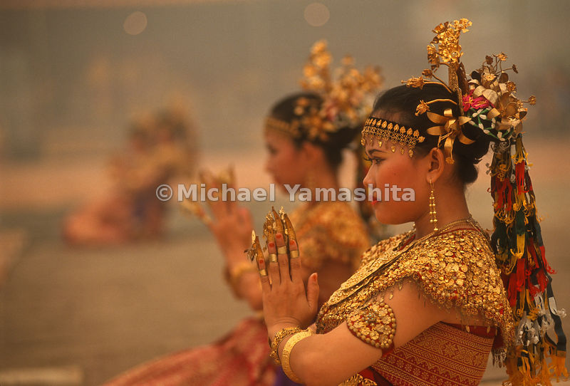 Female dancers engage in a dance routine that is native to Indonesia.
