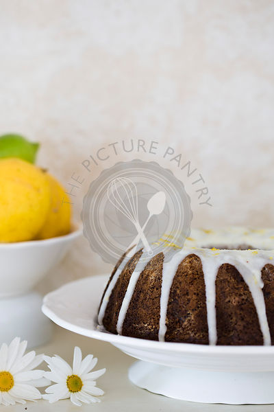 Round mould iced date and walnut cake served on white plate, with lemons in background