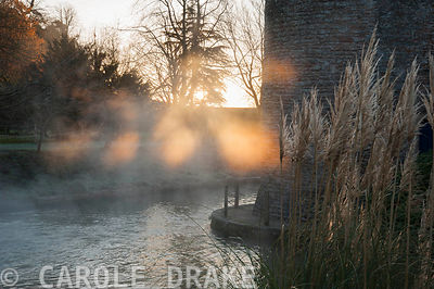 Early morning sun illuminates mist rising from spring water tumbling into the moat around the Bishop's Palace in Wells on a November morning