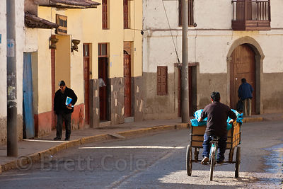 A bread delivery man pedals his tricycle along an empty street at 6:00am in Cusco, Peru
