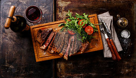 Sliced grilled beef barbecue Striploin steak with arugula salad and Red wine on dark background