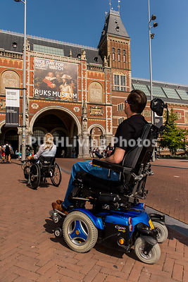 Couple using power wheelchairs exploring a museum in Amsterdam