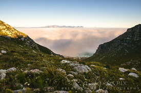 Fog over False Bay viewed from Muizenberg Peak (Farmer Peck's Valley) with sea and village at foot of mountain visable below cloud, distant mountains visable above cloud