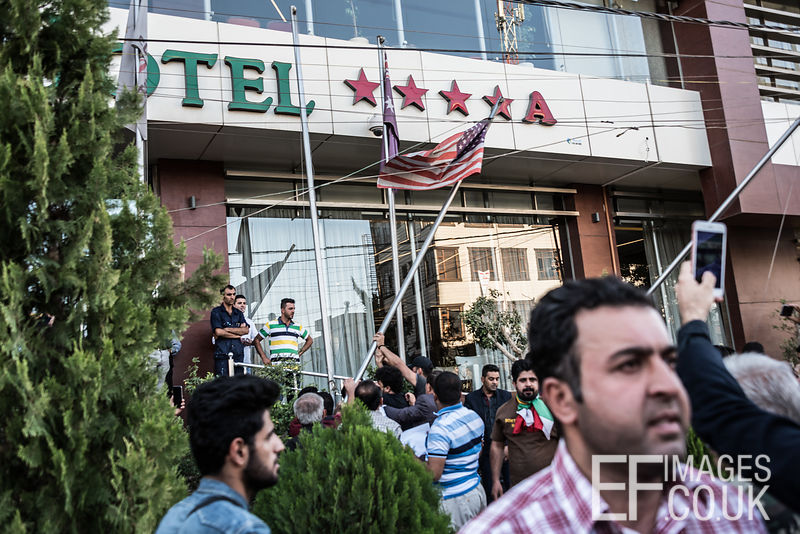 Kurds displaced from Kirkuk by the ongoing conflict, between Iraq allied with Iranian backed Militia group Hashd al Shaabi and the semi autonomous Kurdistan region, tear down the american flags outside the Classy Hotel in Erbil. They are angry that America and the international community did not step in when Iraqi Forces and Hashd al Shaabi entered Kirkuk on the 16th October. Erbil, Iraq