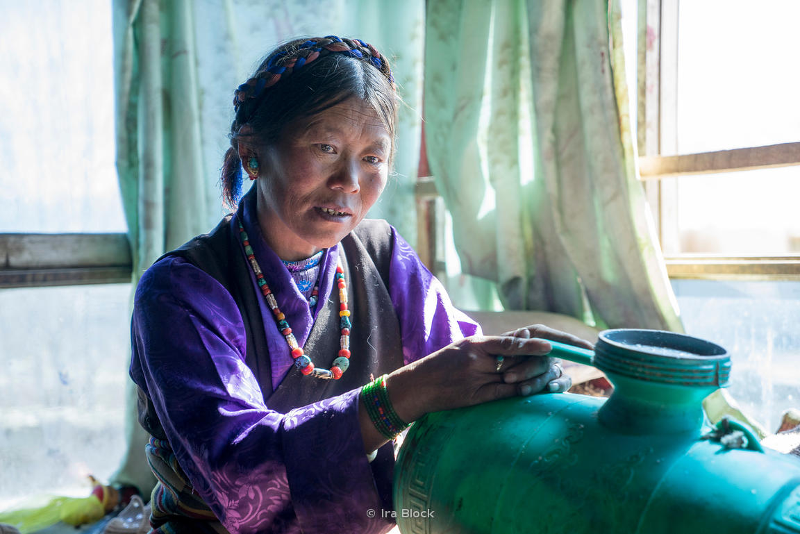 Portrait of a local farm family in the village of Nadang near Shigatse, Tibet. She is churning butter.