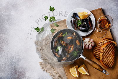 Mussels in cooking pan with parsley and wine on white background copy space