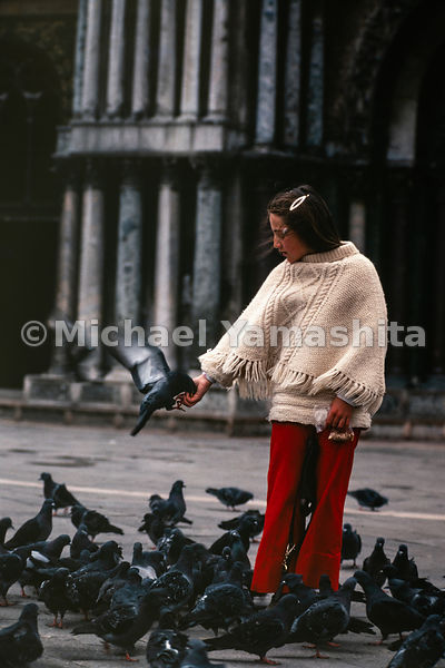 A girl feeds a pigeon while many others surround her. Venice, Italy, March, 1978.